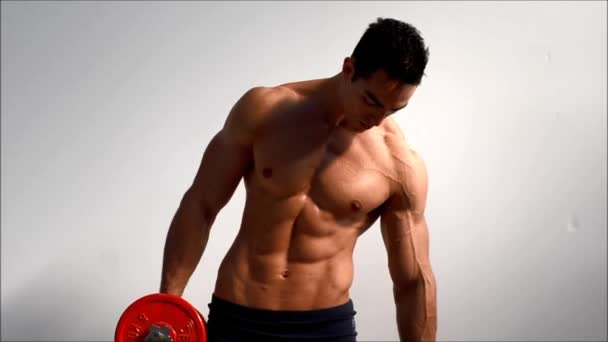 Young handsome male bodybuilder training obliques and abs muscles with dumbbells