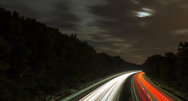 Long time exposure freeway cruising car light trails streaks of light speed highway moon cloudy