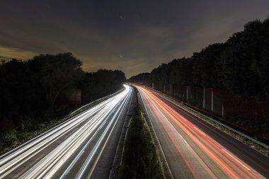 Long time exposure freeway moon cruising car light trails streaks of light speed highway