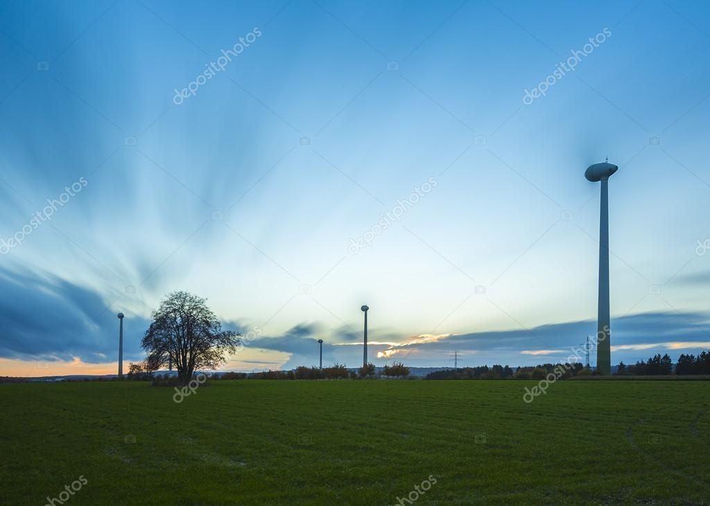 Wind turbine wind wind energy wind power wheels field sunset sky clouds dusk blurred