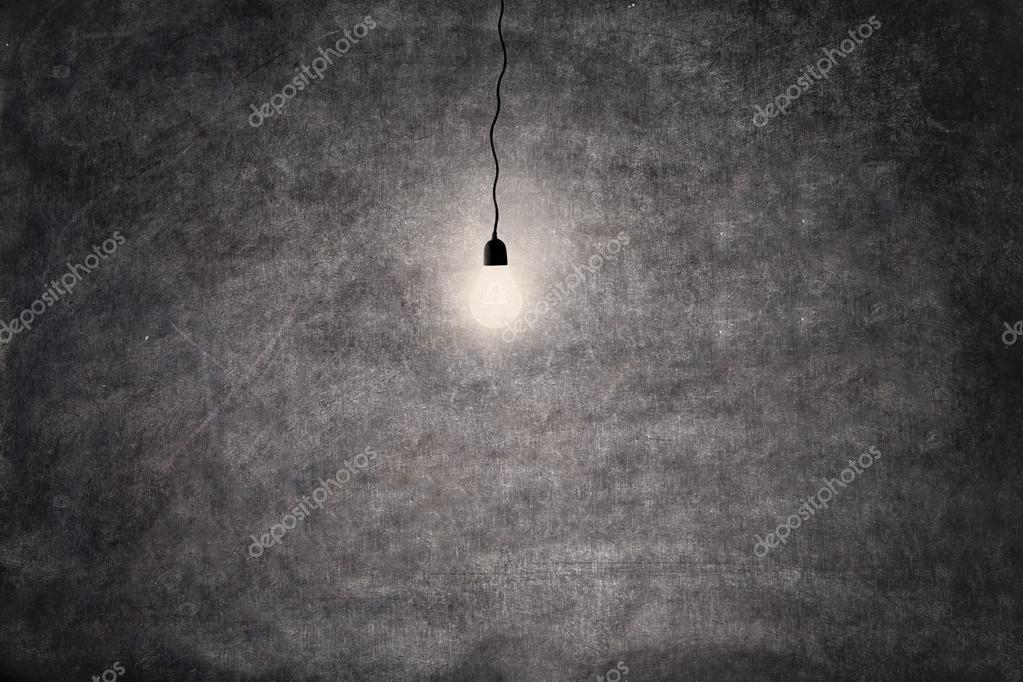 Bright light bulb on blackboard