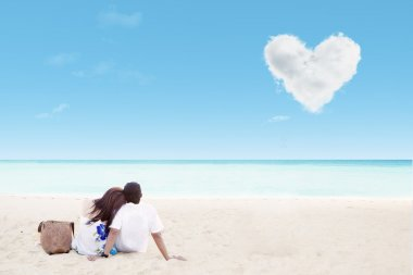 Enjoying honeymoon at white sand beach with love cloud