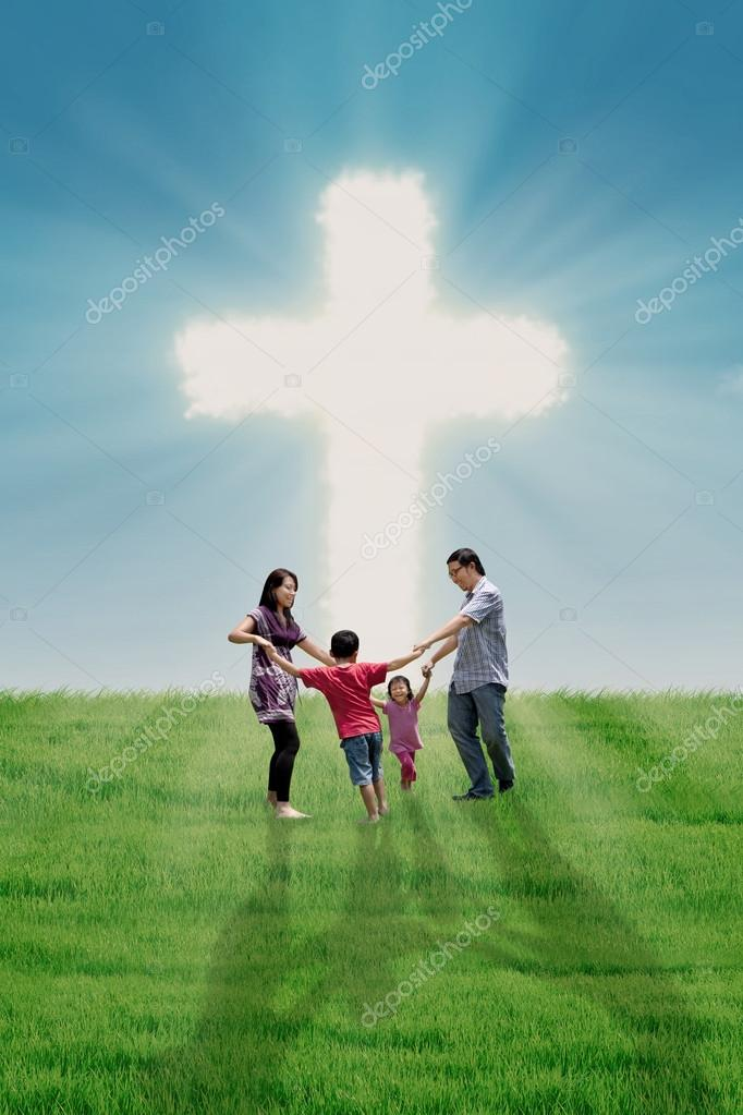 Christian family at bright Cross