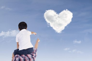 Father and son watch heart clouds