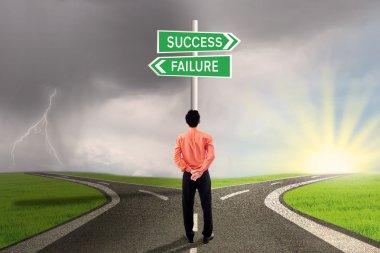Businessman choosing success or failure road