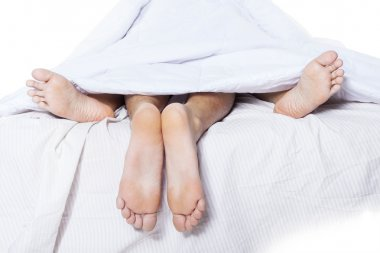 Close-up of couple feet in bed