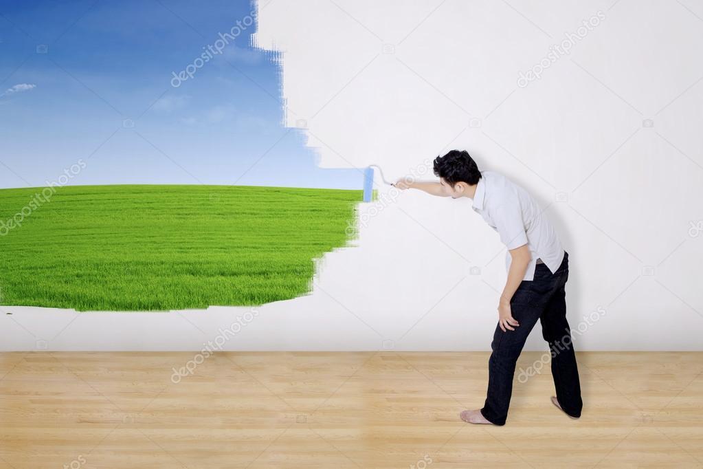 Boyfriend painting green field on wall