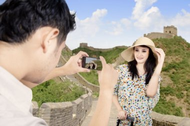 Tourist posing in front of Great Wall in China