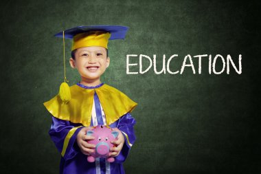 Happy boy with scholar gown and piggy bank