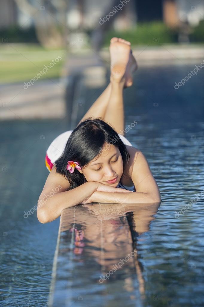 Beautiful woman relaxing at luxury pool resort