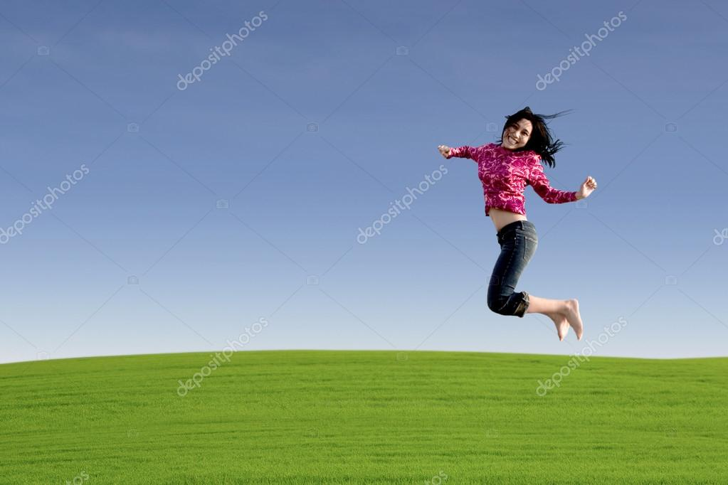Happy entreprenur jumping over green field