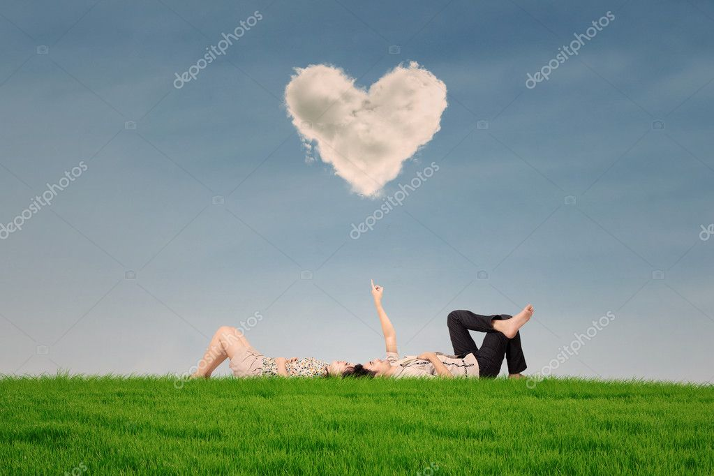 couple passer des vacances sous les nuages de c ur dans le parc photographie realinemedia. Black Bedroom Furniture Sets. Home Design Ideas