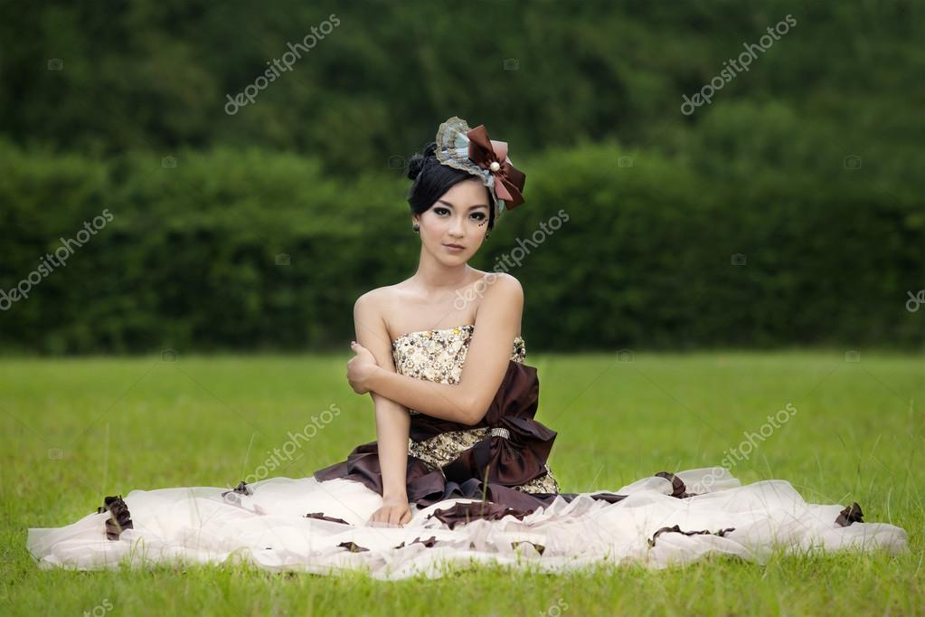 Beautiful lady in gown on green field
