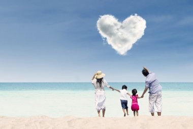 Asian family looking at heart cloud at beach