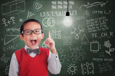 Asian boy has idea under lit bulb in classroom