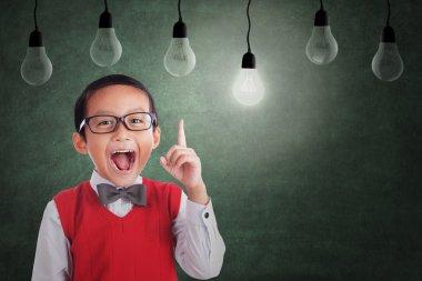 Asian boy has idea under light bulb in class