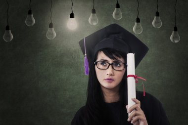 Beautiful female graduate with certificate under lamps