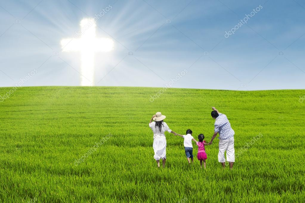 Christian family on green field