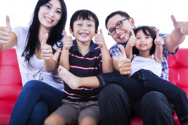 Isolated asian family showing thumbs up