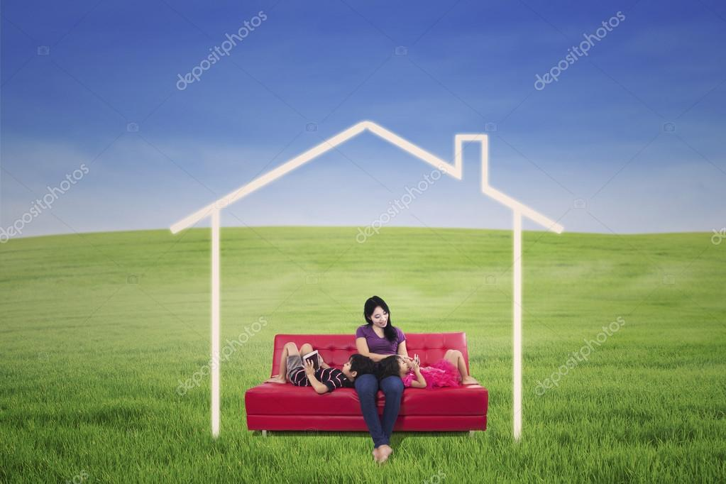 Mother and children on green field with dream house