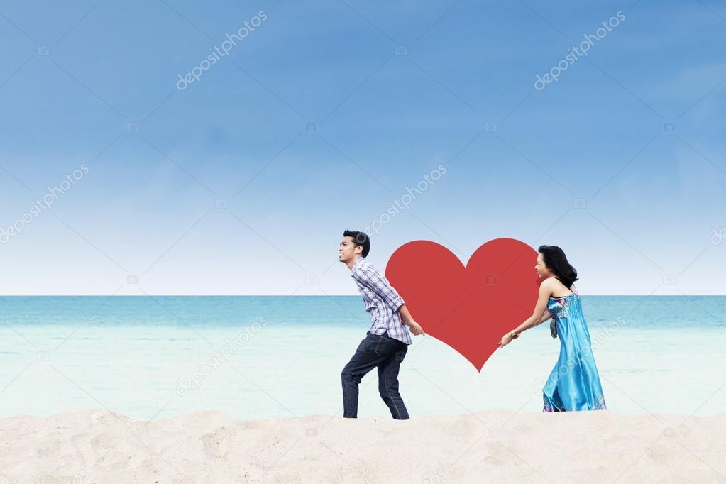 Asian couple bring heart card at beach