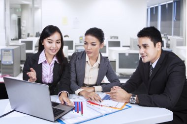Three asian business team with laptop at office