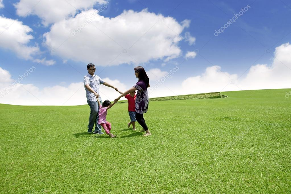 Happy asian family playing on the field