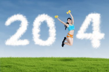 2014 New Year clouds and fitness woman jumping