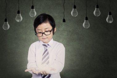 Young boy holding a light bulb