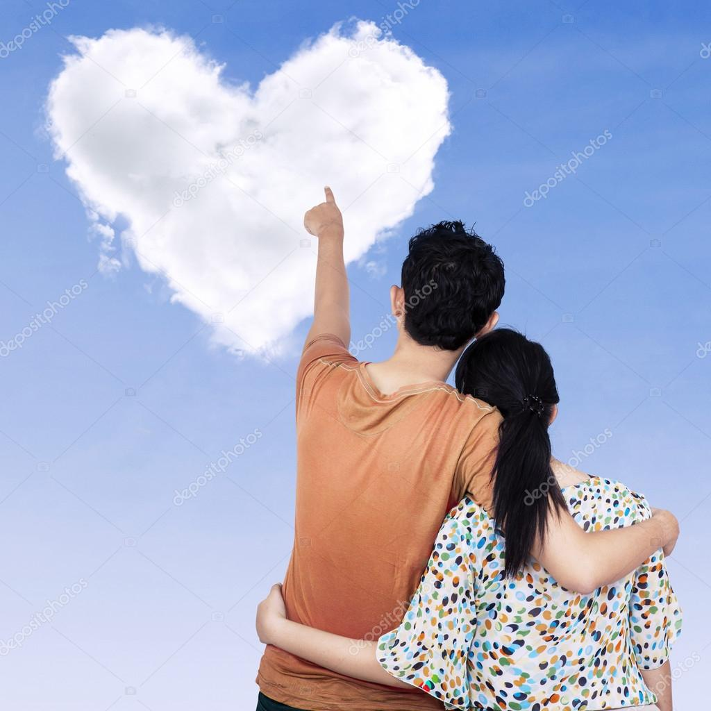 Young couple pointing at heart