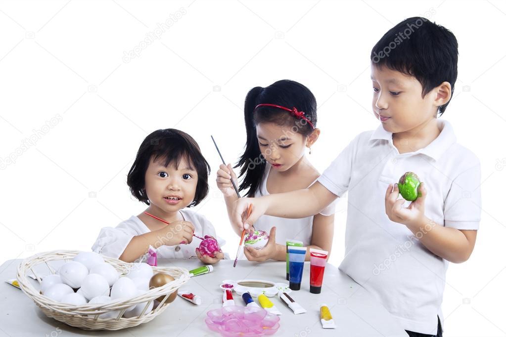 Happy children painting easter eggs