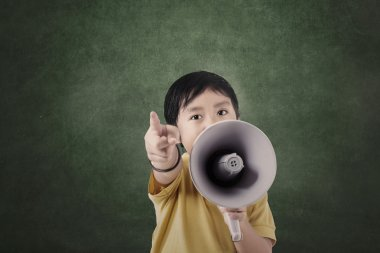 Boy and megaphone in front of blank board