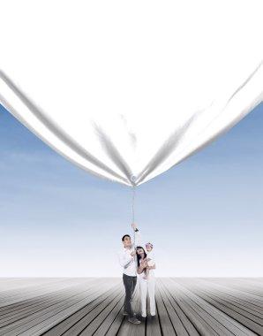 Family pulling blank banner