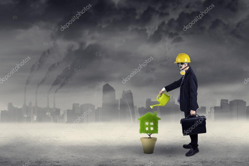 Businessman watering plant under air pollution 1