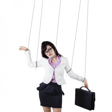 Businesswoman controlled by strings isolated