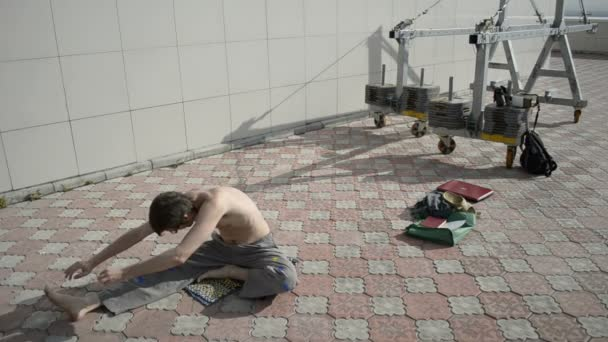 Man practices yoga on the roof. Stretching back, stretching hands.