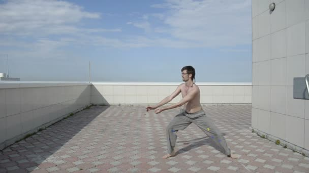 Man practices yoga on the roof. Complex military exercises ninja.