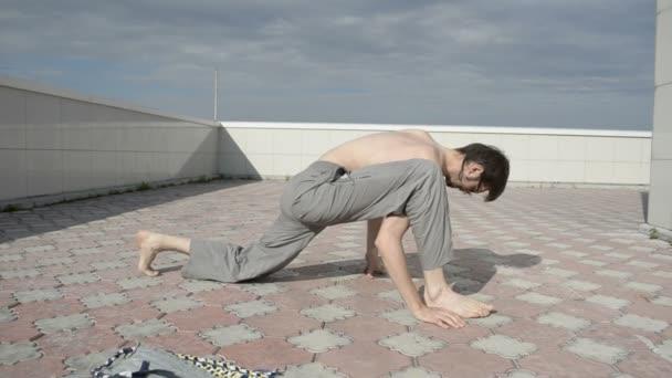 člověk praxe jógy na střeše. táhnoucí se pod kolenem