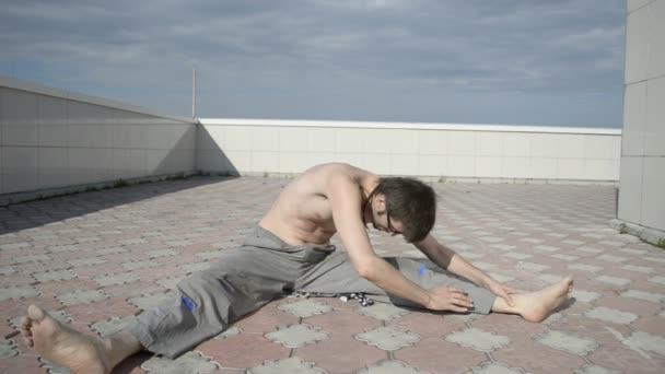 člověk praxe jógy na střeše. protahování zad, nohy od sebe