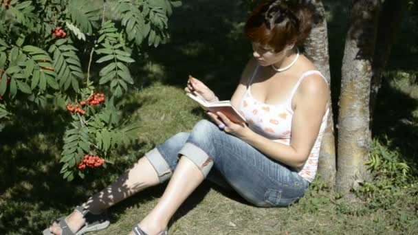 A student reads a book in the park sitting on grass