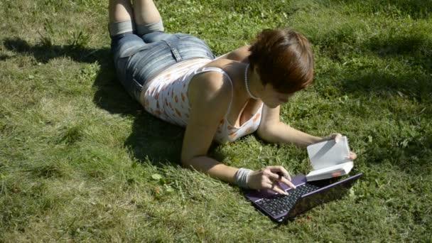 student ležící na trávě, pomocí přenosného počítače a notebooky