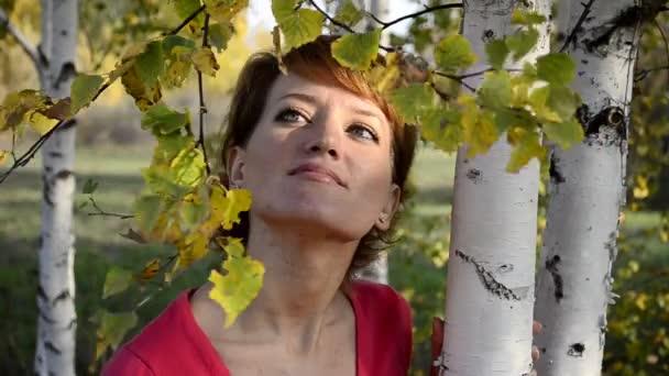mladá žena stojící v podzimním parku pod břízy