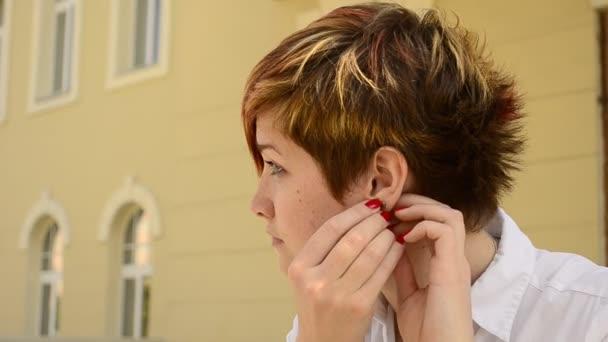 mladá žena nosí náušnice a dívá do zrcadla
