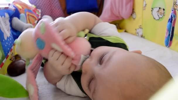 je dítě v postýlce s hračkami