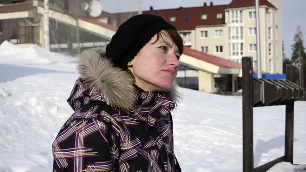 mladá žena sedící na lavičce v lyžařském středisku