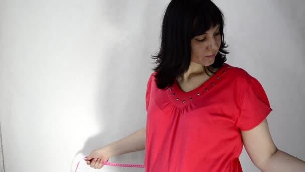 mladá těhotná žena měření břiše s páskou