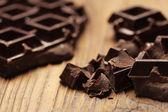 Fotografia pezzi di cioccolato scuro su uno sfondo in legno