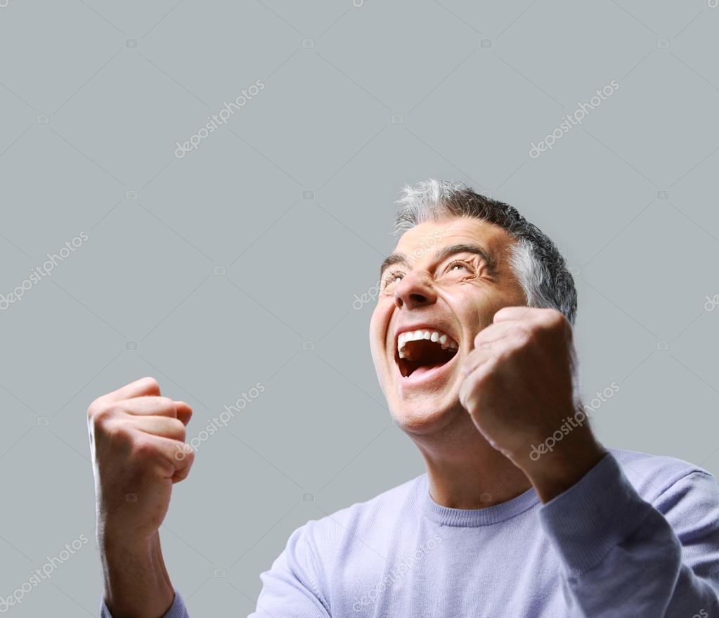 Portrait of excited mature man, raising his fists on grey background.