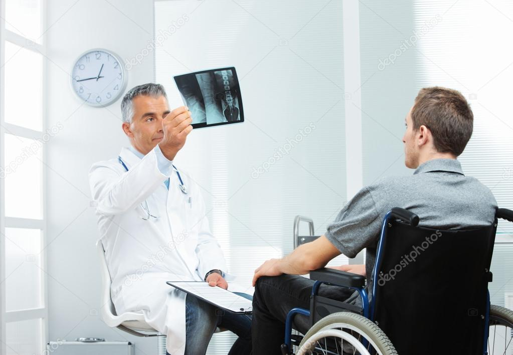 Young patient with mature doctor discussing x-ray