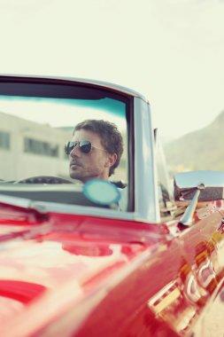 Handsome man driving a convertible car